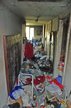 The hallway of a Melbourne apartment belonging to a person with a hoarding problem following a fire.