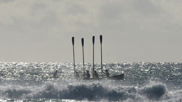 Members of Maroochydore Surf Life Saving Club hold up their paddles during a memorial service for Matthew Barclay.