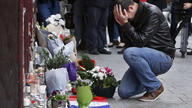 A man holds his head in his hands as he lays flowers in front of the Carillon cafe, in Paris, on November 14.