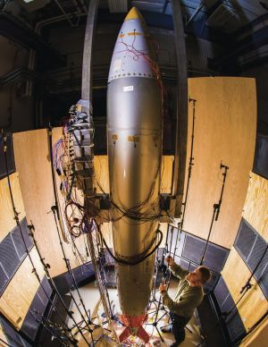Sandia Labs mechanical engineer Ryan Schultz adjusts a microphone for an acoustic test on a B61-12 nuclear bomb ...