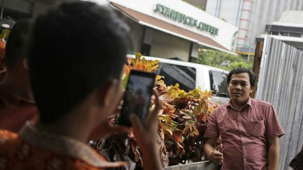 A man poses for a photo on Friday outside the Starbucks cafe where Thursday's attack occurred in Jakarta.