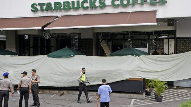 Police and officials gather in the parking lot outside the damaged Starbucks cafe where Thursday's attack occurred in ...