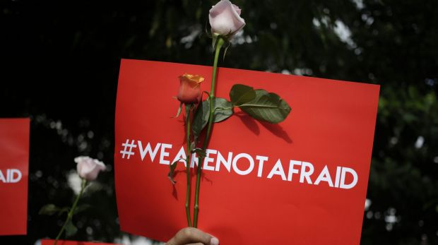 An activist holds a placard during a rally condemning the Jakarta attacks.