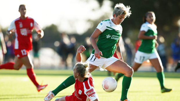 Canberra United striker Michelle Heyman runs with the ball over Adelaide's Grace Abbey.