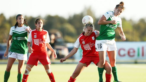 Grace Abbey of Adelaide competes with Canberra United's Tegan Riding for the ball.