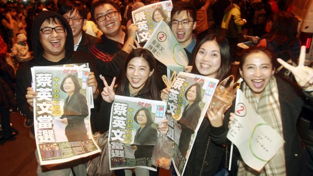 Supporters of the Democratic Progressive Party's Tsai Ing-wen display newspaper headlines featuring the newly elected ...
