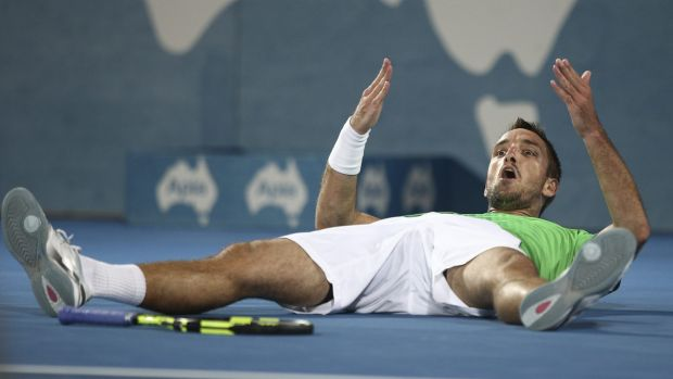 Flat out: Viktor Troicki lies down on the court as he celebrates winning the men's final.