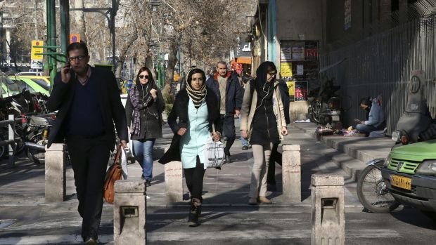 Pedestrians cross a street in central Tehran, Iran, on Saturday, ahead of crippling sanctions being lifted.
