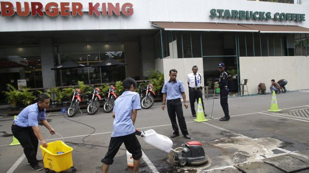 Workers clean up the spot where the militants involved in Thursday's attack were killed in Jakarta, Indonesia.