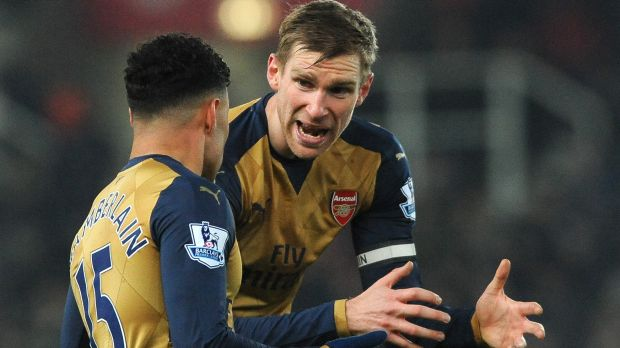 Frustration: Arsenal captain Per Mertesacker, right, and Alex Oxlade-Chamberlain plot a way through the Stoke defence.