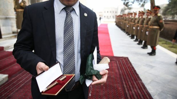 A staff member of the Presidential Palace holds the pen that Malcolm Turnbull presented to the President of Afghanistan, ...