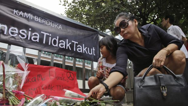 A woman lays flowers outside the Starbucks cafe after January's terrorist attack in Jakarta.
