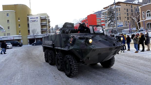 Pedestrian watch as an armoured Swiss military police vehicle drives past Davos Dorf railway station ahead of the World ...