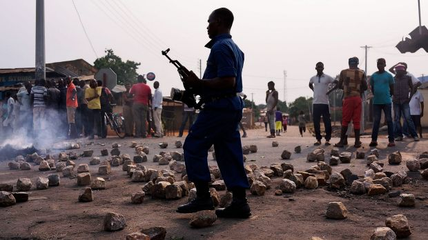 A Burundian policeman walks through rubble during protests against the governing party in June last year. Burundi came ...