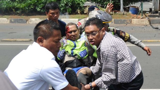 People carry an injured police officer near the site where an explosion went off at a police post during the Jakarta attacks.