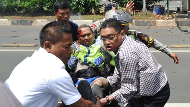 People carry an injured police officer near the site where an explosion went off at a police post during the Jakarta ...
