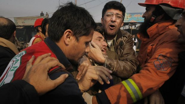 People comfort a man who lost a family member in a suicide attack, in Peshawar, Pakistan.