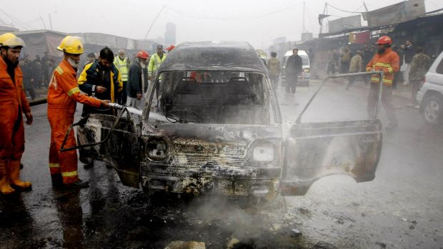 Pakistani fire fighters try to extinguish a vehicle on fire following a suicide blast, in Peshawar, Pakistan.