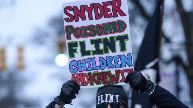 Mike Ahrens of Muskegon poses for photo with his sign about Flint's water crisis in Ann Arbor, Michigan.
