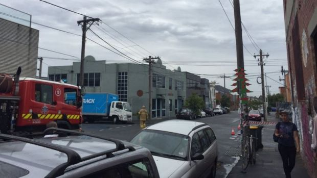 Fire crews attend to the burning fire pole outside PBS's studio in Collingwood on Thursday.