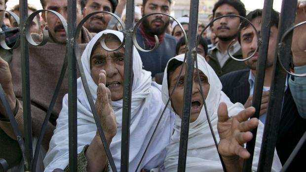Pakistani family members wait outside a local hospital where injured students were taken.