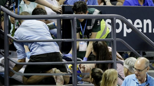Medical staff attend to the injured fan on a stairwell