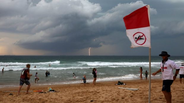 Wollongong City Council Lifeguard Jake Spooner raises the no swim flag, closing Austinmer beach as a Southerly storm ...