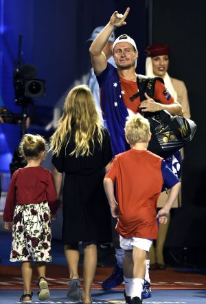 Family affair: Lleyton Hewitt waves farewell to the Rod Laver Arena crowd as he leaves, followed by his children.