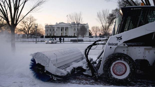 A worker with the National Park Service sweeps snow along Pennsylvania Avenue in front of the White House in Washington, ...
