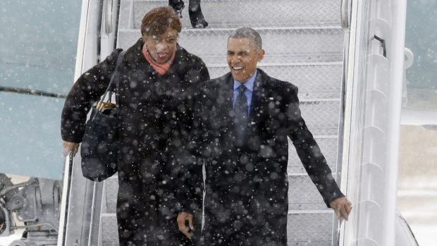 President Barack Obama, right, arrives in the snow on Air Force One at the Detroit Metropolitan Airport. His helicopter, ...