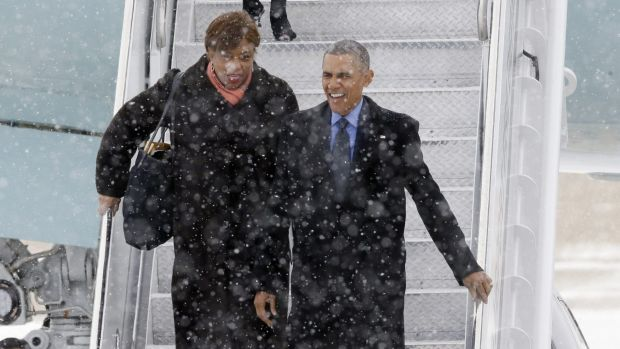 US President Barack Obama, right, arrives in the snow on Air Force One at the Detroit Metropolitan Airport on Wednesday.