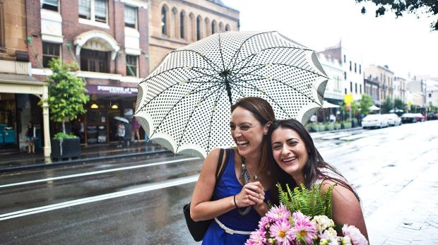 It's not all bad: Lauren Sullivan and Sarah Disano of Clovelly do their best to find shelter from the rain.