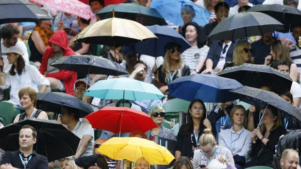 Rain-soaked spectators wait for the Rod Laver roof to close on Friday.