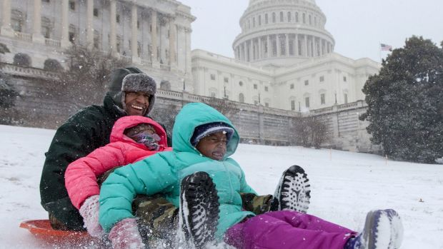 Bashon Mann and his children sled down a hill on Capitol Hill in Washington as snow falls. With a major blizzard ...