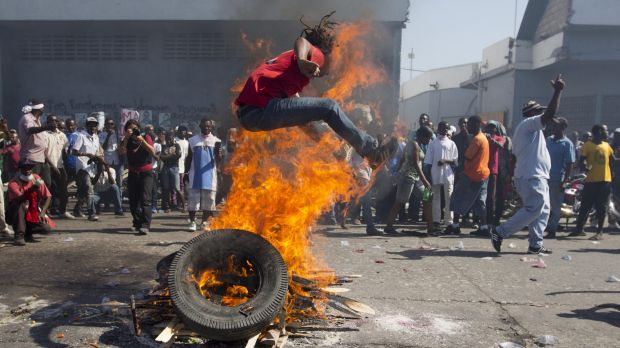 A protester jumps over a burning barricade in the capital.