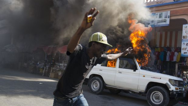 A protester runs past a burning car during a demonstration to demand the cancellation of the run-off elections in ...