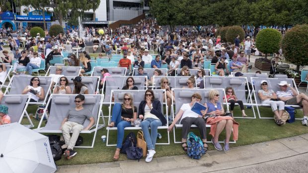 People relax as they watch the tennis at the big screen at Melbourne Park.