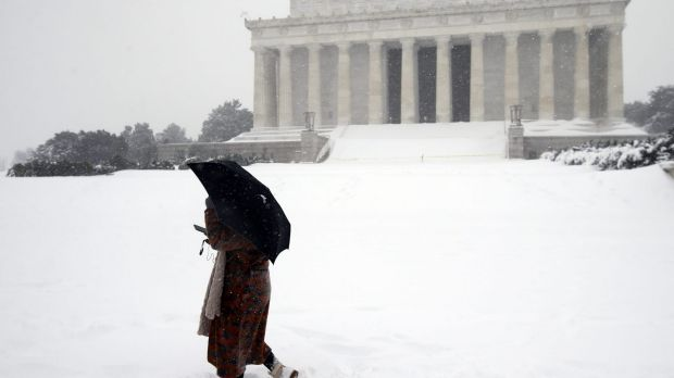Jasmine Wang walks through snow in front of the Lincoln Memorial in Washington.