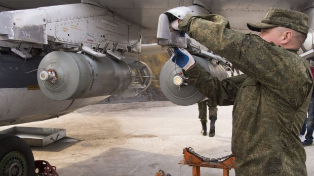 A Russian air force technician attaches a bomb to a Russian ground attack jet at an air base in Syria.