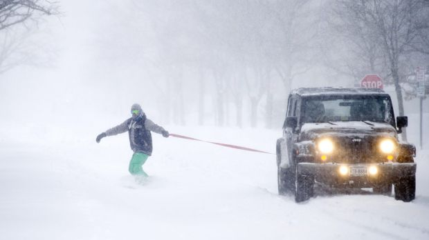 Gary Utley, 27, of Alexandria, snowboards behind a Jeep driven by his friend, as snow falls, in Alexandria, Virginia on ...