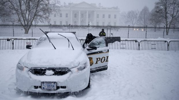 A uniformed Secret Service officer opens a car door on a patrol car that was frozen shut during blizzard conditions.