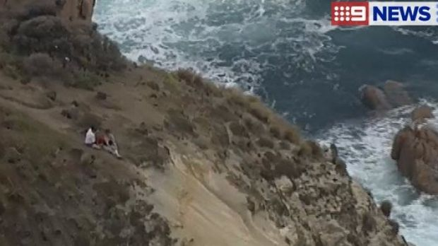 The couple sat on the cliff until they could be pulled to safety.
