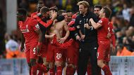 Liverpool's Adam Lallana, center, celebrates with his teammates and manager Jurgen Klopp, third right, after scoring his ...