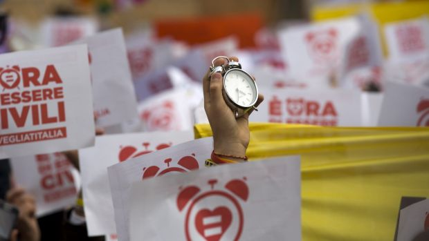 An activist holds up an alarm clock during a demonstration in Rome, symbolically asking Italian MPs to wake up and ...