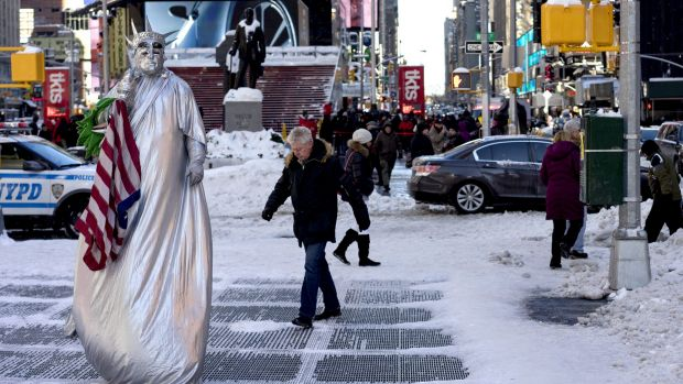 A costumed character, along with pedestrians, navigate sometimes slippery conditions in New York's Times Square Sunday ...