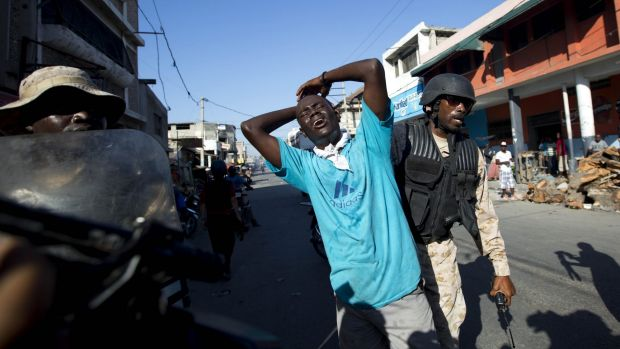 A man is detained by police in Port-au-Prince during an anti-government protest.