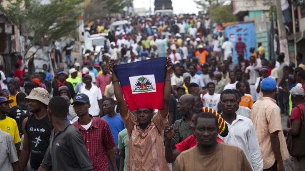 Anti-government protesters hold up the Haitian flag. Annual Carnival celebrations have been sidelined by the political ...