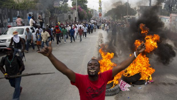 Demonstrators walk past a burning barricade in Port-au-Prince, the Haitian capital.
