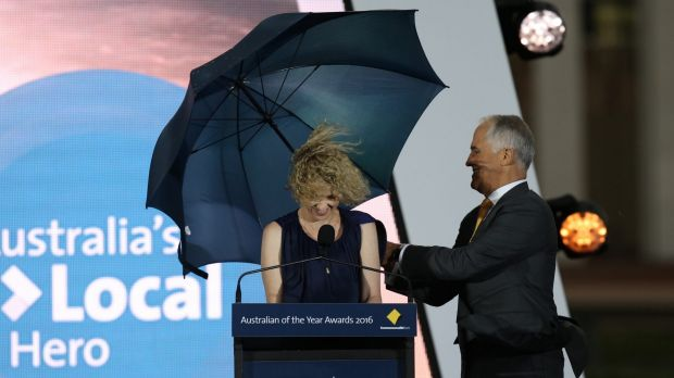 Local Hero of the Year Catherine Keenan is shielded by Prime Minister Malcolm Turnbull at a windy Parliament House.