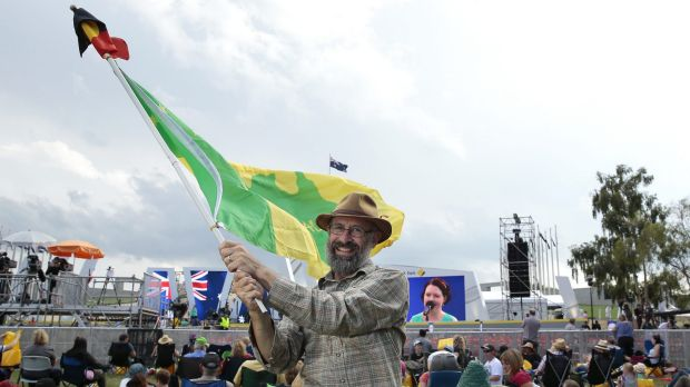 Ian Robertson of Morisset waves the Aboriginal and a Green and Gold flag.